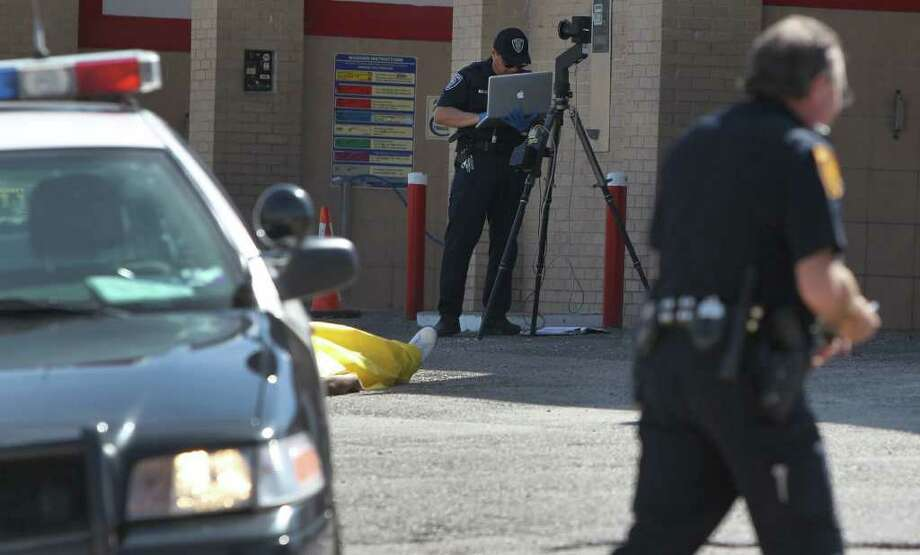 San Antonio police work the scene of a fatal shooting at a car wash on Spriggsdale near East Commerce. Two people died and a third person was wounded in a fight that escalated into gunfire, with suspected shooters driving away in a blue vehicle, police said. Photo: John Davenport/Express-News