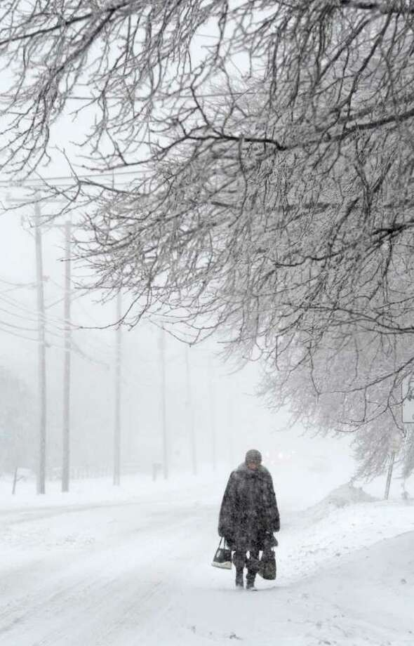 A pedestrian Monday morning is forced to walk in the road on Sand Creek Road as another winter storm hit the Capital Region. (Skip Dickstein / Times Union) Photo: SKIP DICKSTEIN / 2008