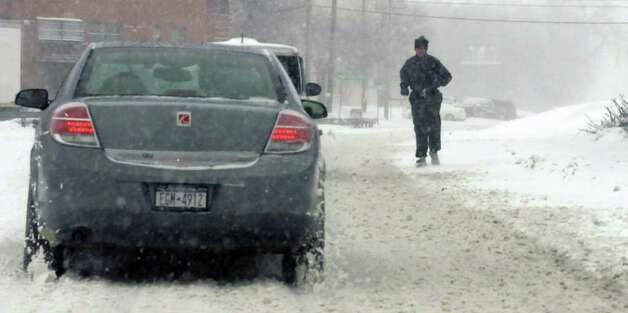 A runner braves the snow and sleet in Albany, NY, on Monday, March 7, 2011, as another winter storm hit the Capital Region.  (Paul Buckowski / Times Union) Photo: Paul Buckowski / 00012307A