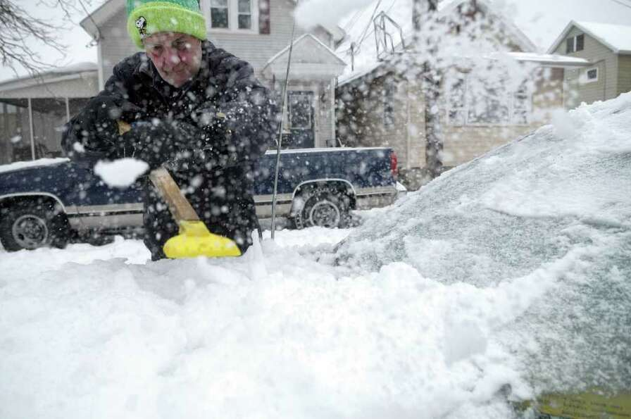 Henry Vanderwerken of Watervliet, NY, clears his car of ice on Monday, March 7, 2011, as another win