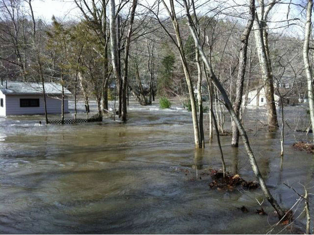 Water flows through Roosevelt Drive in Monroe, Conn. on Monday, March 7, 2011 after heavy rain left the region with significant flooding.