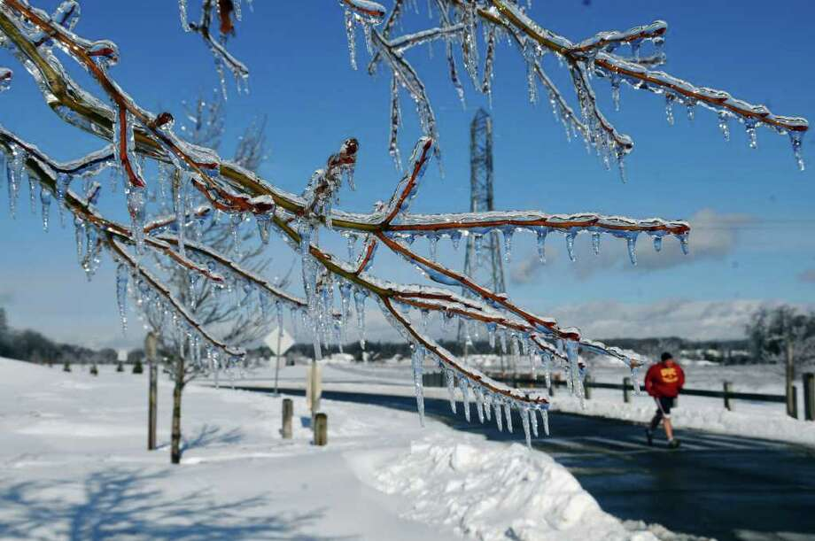 """Paul Donnini of Colonie takes his daily run in the Crossings of Colonie park, past trees covered in ice on Monday Mar. 7, 2011 in Colonie, NY, before heading to his job as a waiter later in the day.  """"Yesterday was the most brutal run of the year,"""" said Donnini of running in a heavy rain storm, while saying that Monday's run was beatiful. """"Today it was so beautiful, its just nature's irony,"""" he said. He spoke of running past trees in the park, that were like a """"forest full of icicles."""" ( Philip Kamrass / Times Union ) Photo: Philip Kamrass"""