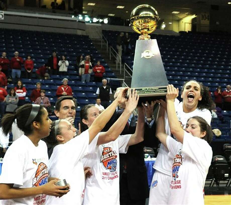 Members of the Marist  women's basketball team hold up the winners' trophy after defeating  Loyola in an NCAA college basketball game during the  Metro Atlantic  Athletic Conference basketball tournament in Bridgeport, Conn., Monday,  March 7, 2011. No. 19 Marist defeated Loyola 63-45 to win the  tournament. Photo: Associated Press, Bob Child