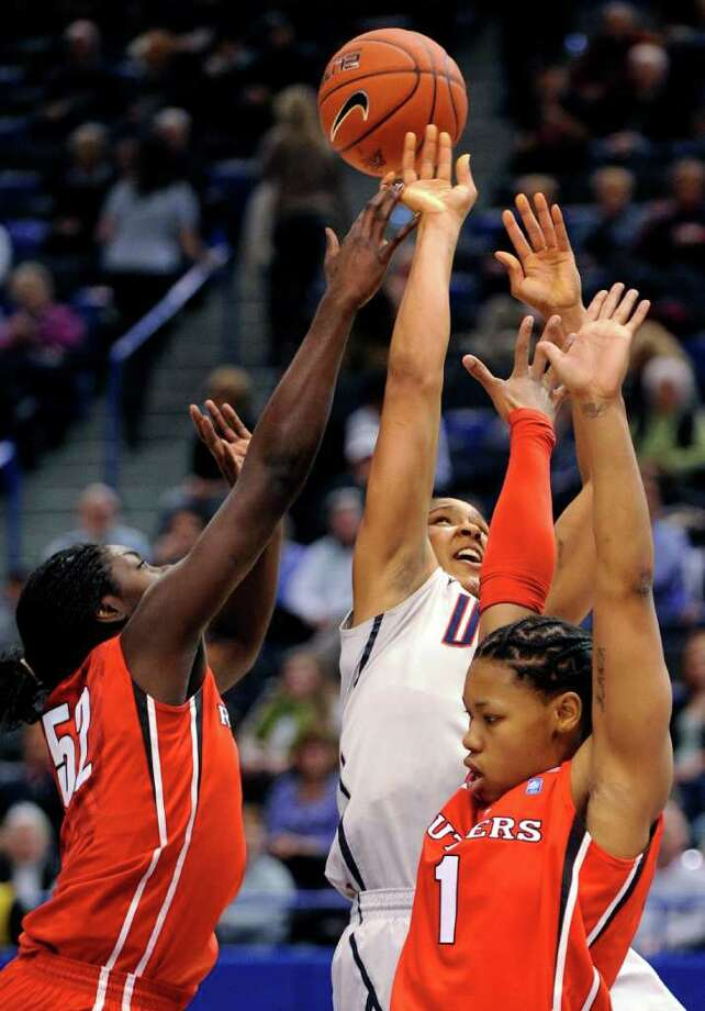 Connecticut's Maya Moore, center, is fouled as she drives past Rutgers' Chelsey Lee, left, and Khadijah Rushdan during the first half of an NCAA college basketball game in the semifinals of the Big East tournament in Hartford, Conn., on Monday, March 7, 2011. (AP Photo/Fred Beckham) Photo: AP