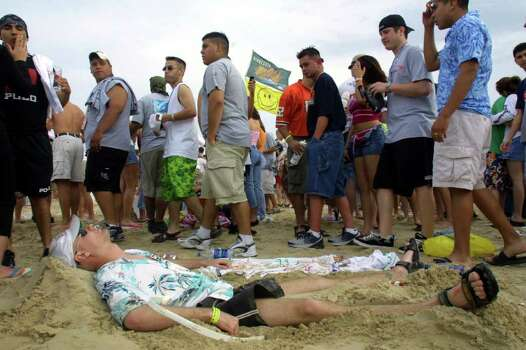 386746 11: A student lies on the beach at South Padre Island, Texas March 16, 2001 during the annual rite of Spring Break. Some 125,000 revelers, mostly college students on a break from classes, descend on the Texas beach each year for an alcohol-soaked week of sun, sand and partying. (Photo by Joe Raedle/Newsmakers) Photo: Joe Raedle, Getty Images / Getty Images North America