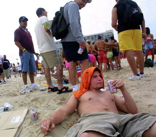 386746 27: A man drinks beer on the beach at South Padre Island, Texas March 16, 2001 during the annual rite of Spring Break. Some 125,000 revelers, mostly college students on a break from classes, descend on the Texas beach each year for an alcohol-soaked week of sun, sand and partying. (Photo by Joe Raedle/Newsmakers) Photo: Joe Raedle, Getty Images / Getty Images North America