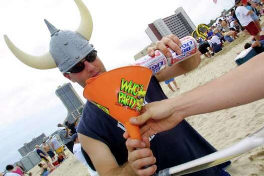 386746 33: A man prepares to drink beer from a funnel on the beach at South Padre Island, Texas March 16, 2001 during the annual rite of Spring Break. Some 125,000 revelers, mostly college students on a break from classes, descend on the Texas beach each year for an alcohol-soaked week of sun, sand and partying. (Photo by Joe Raedle/Newsmakers) Photo: Joe Raedle, Getty Images / Getty Images North America
