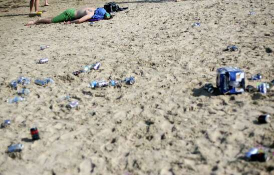 SOUTH PADRE ISLAND, TX - MARCH 25:  A student lays on the beer can covered beach at South Padre Island, Texas March 25, 2008 during the annual ritual of Spring Break.  The South Texas island is one of the top Spring Break destinations and attracts students from all over the country. Photo: Rick Gershon, Getty Images / 2008 Getty Images