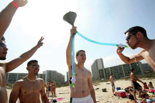 SOUTH PADRE ISLAND, TX - MARCH 25:  Students from the University of Texas El Paso drink from a beer funnel on the beach at South Padre Island, Texas March 25, 2008 during the annual ritual of Spring Break.  The South Texas island is one of the top Spring Break destinations and attracts students from all over the country. Photo: Rick Gershon, Getty Images / 2008 Getty Images