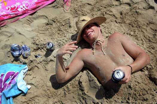 SOUTH PADRE ISLAND, TX - MARCH 25:  A drunken student lays half buried in sand on the beach at South Padre Island, Texas March 25, 2008 during the annual ritual of Spring Break.  The South Texas island is one of the top Spring Break destinations and attracts students from all over the country. Photo: Rick Gershon, Getty Images / 2008 Getty Images