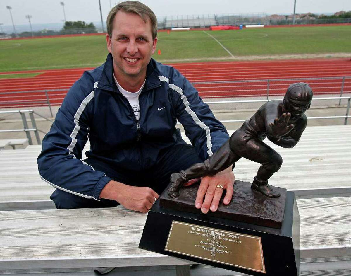 Ty Detmer shows off his 1990 Heisman Trophy before starting his coaching duties at a 2007 football camp at Lake Travis High School near Austin Saturday.  TOM REEL/STAFF