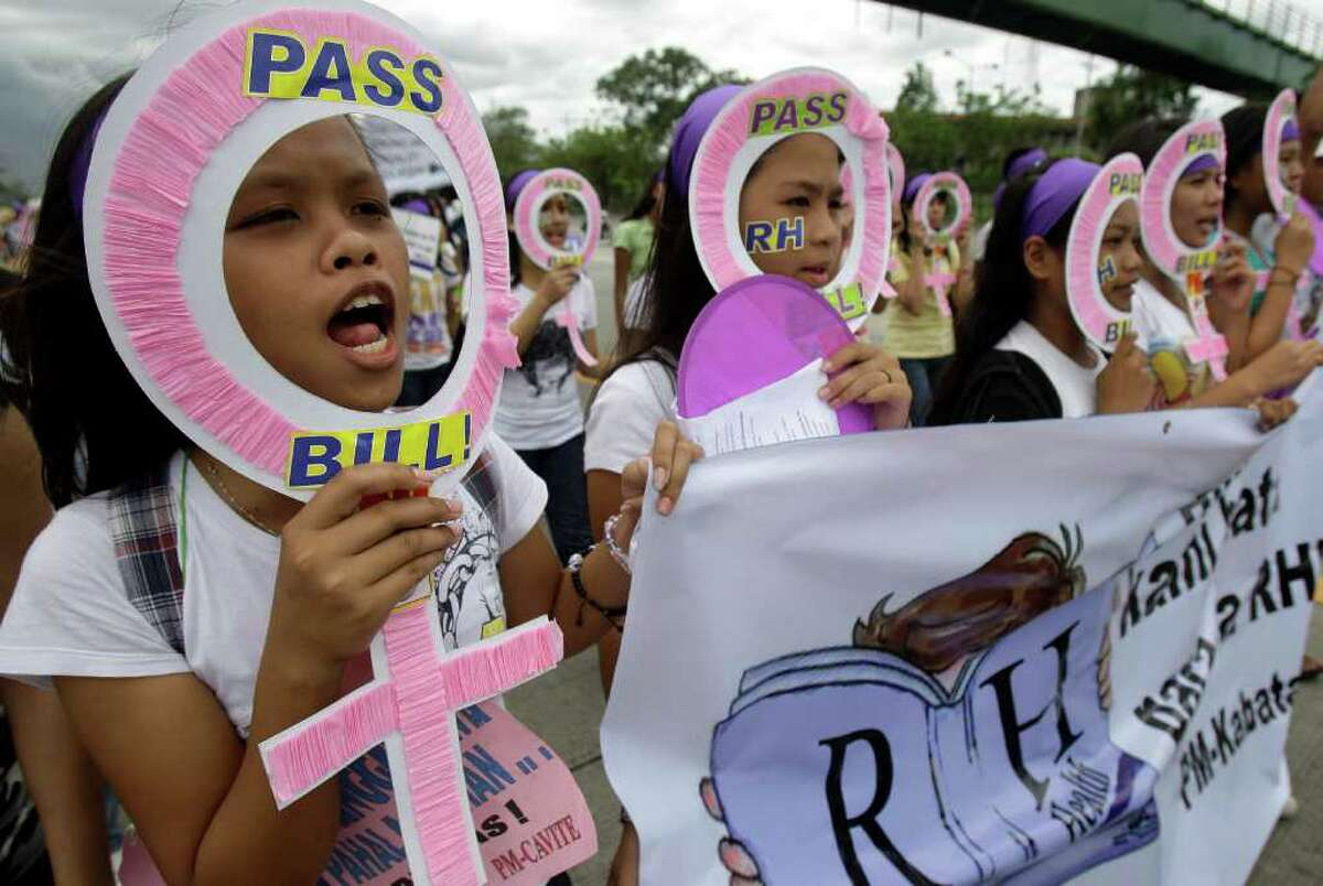 Women protesters hold slogans as they march towards the House of Representatives in suburban Quezon City, north of Manila, Philippines on Tuesday March 8, 2011 to mark the 100th year of International Women's Day. Demonstrators were also calling for support of the passage of the Reproductive Health Bill, a law that guarantees universal access to methods and information on birth control and maternal care. The issue has caused national debates and is being opposed by the influential Roman Catholic church.