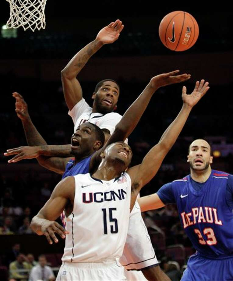 Connecticut's Kemba Walker  (15) and Alex Oriakhi, background top, fight for a loose ball against  De Paul's Krys Faber (33) and Cleveland Melvin during the first half of  an NCAA college basketball game at the Big East Championship, Tuesday, March 8, 2011, at Madison Square Garden in New York.