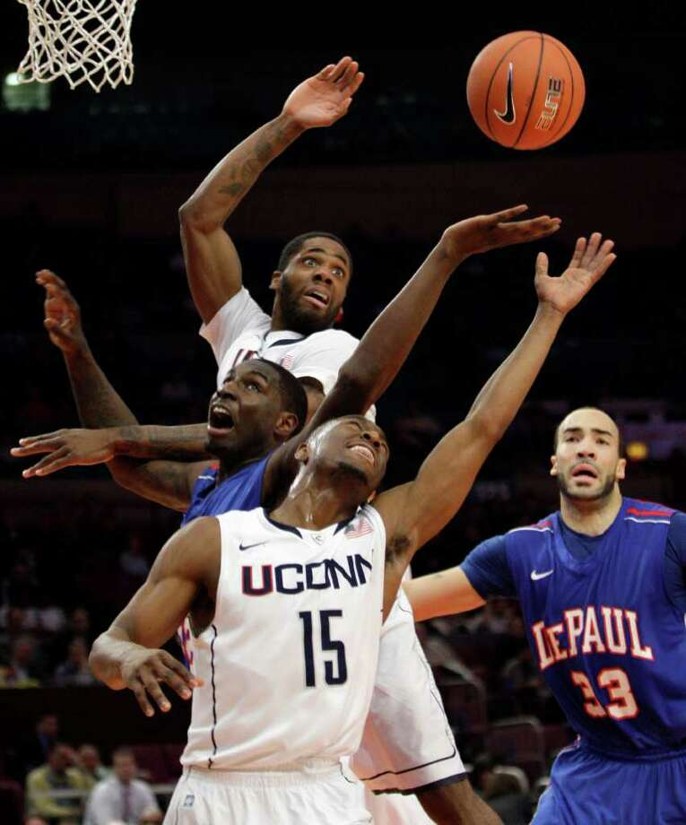 Connecticut's Kemba Walker (15) and Alex Oriakhi, background top, fight for a loose ball against De Paul's Krys Faber (33) and Cleveland Melvin during the first half of an NCAA college basketball game at the Big East Championship, Tuesday, March 8, 2011, at Madison Square Garden in New York.  (AP Photo/Mary Altaffer) Photo: Mary Altaffer, AP / Associated Press