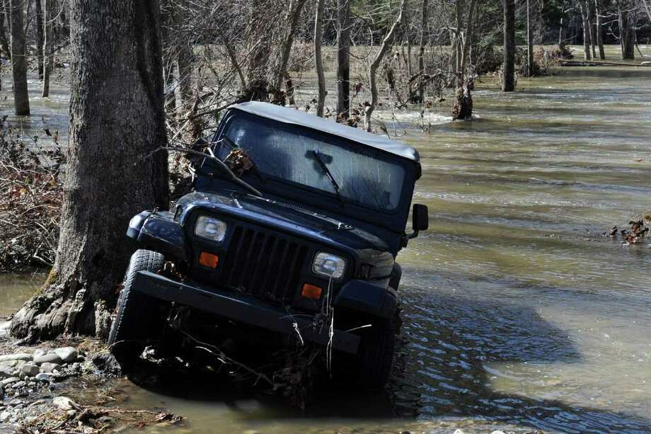 As flood waters on the Housatonic River in Oxford, Conn. receded Tuesday, this Jeep that was submerged in Monday's flooding sits lodged against a tree. Photo: Autumn Driscoll / Connecticut Post