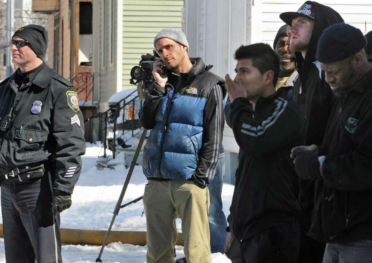 Gunther Fishgold talks on his cell phone as Albany firefighters put out a fire at the building he owns at 139 Dove St. in Albany, NY, on Tuesday, March 8, 2011. Fishgold is also a boxing mangager. Chris Fitzpatrick, second from right, is one of his boxers. (Lori Van Buren / Times Union)