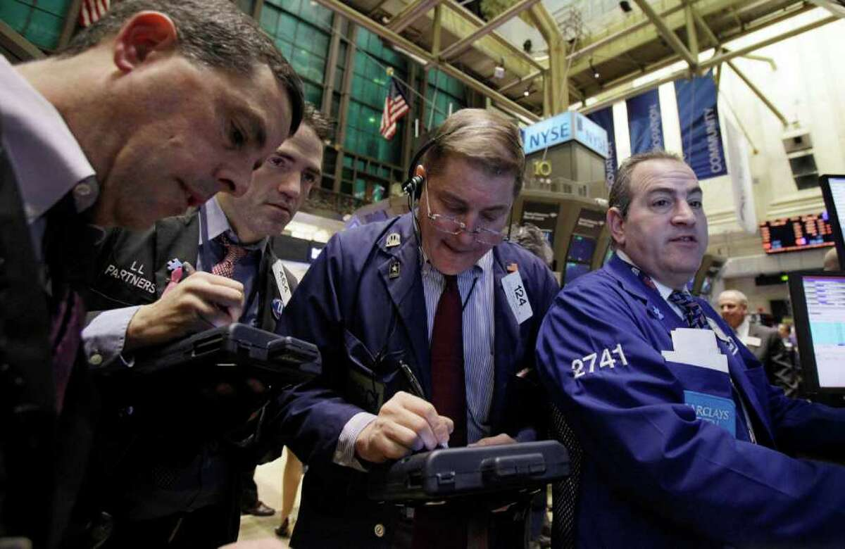 In this Feb. 1, 2011 photo, traders gather at a post on the floor of the New York Stock Exchange. (AP Photo/Richard Drew)