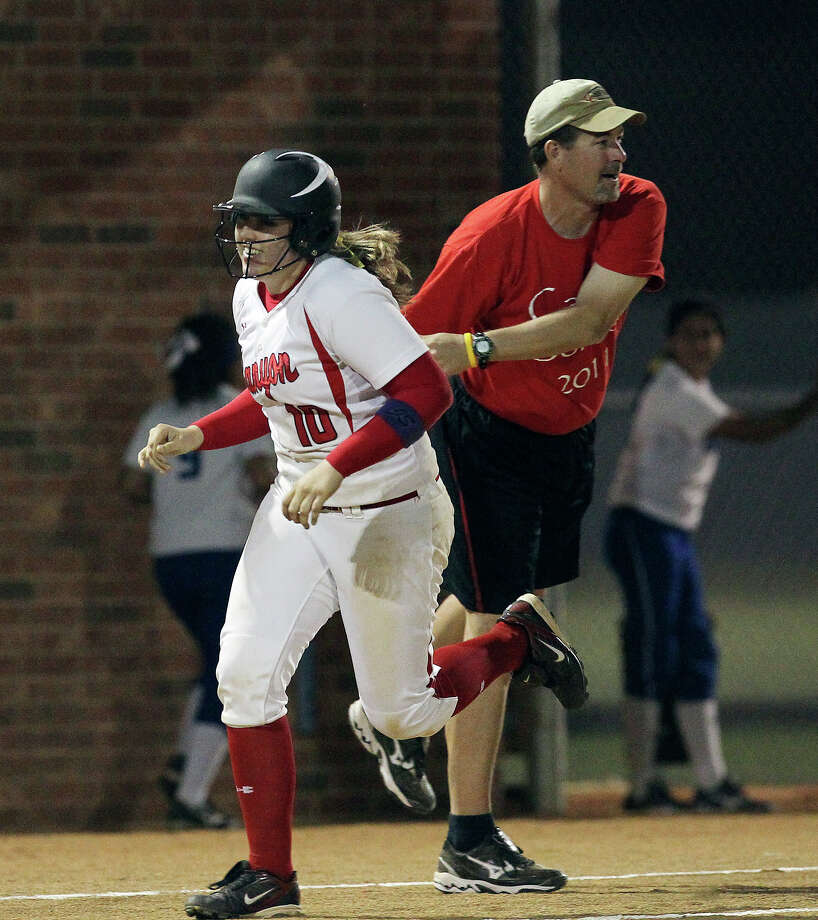 Canyon's Sarah Crockett (10) rounds third base and gets congratulated by coach Kevin Randle after she hit a solo homer in the fifth inning against New Braunfels in softball at Canyon High School on Tuesday, Mar. 8. 2011. Canyon defeated New Braunfels, 6-4. Photo: Kin Man Hui/kmhui@express-news.net / San Antonio Express-News