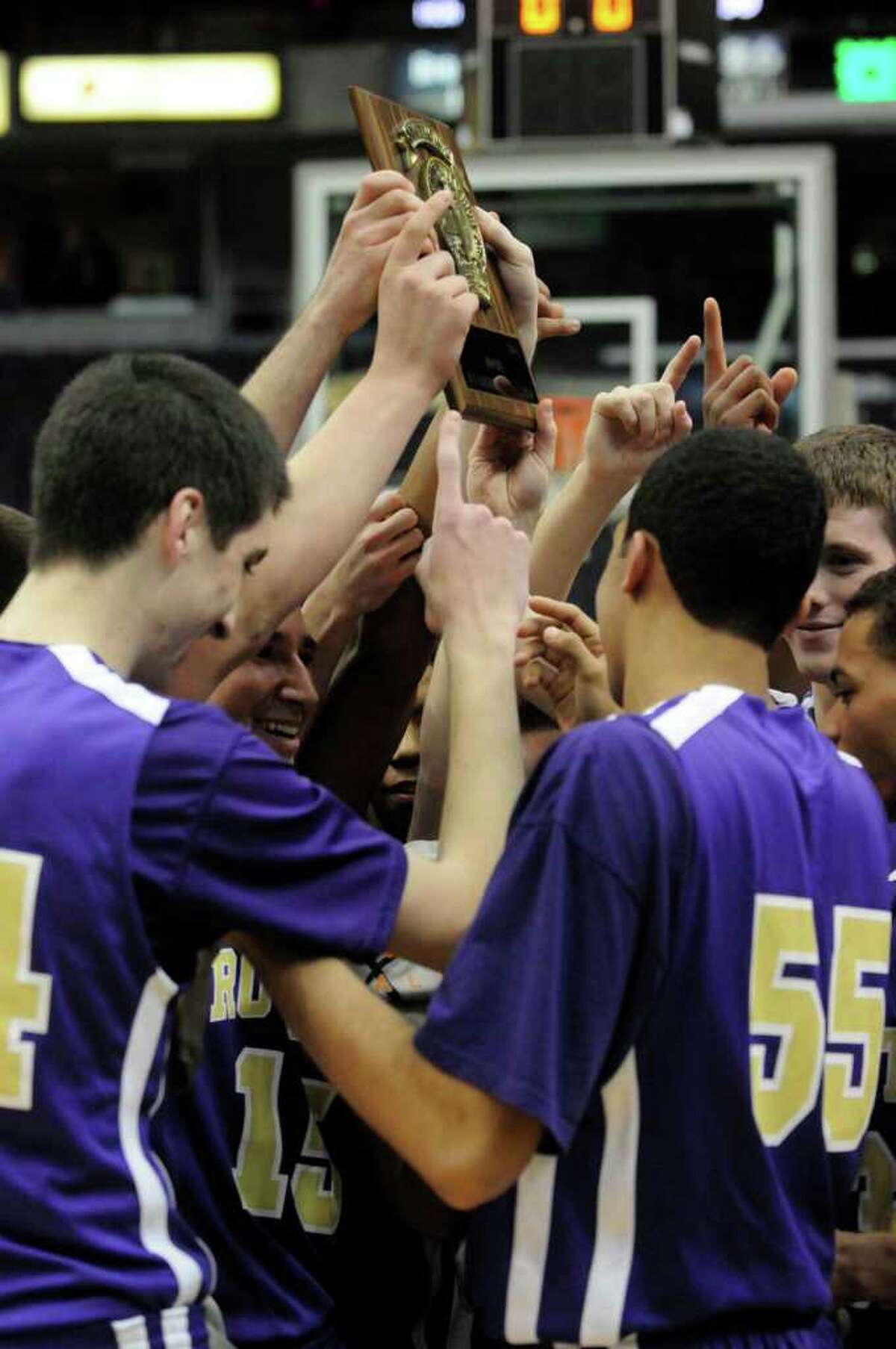 CBA boys varsity basketball team players hold up the championship trophy following their Section 2 Class AA boys basketball finals win 69-46 over Bishop Maginn at the Times Union Center in Albany Tuesday March 8, 2011.( Michael P. Farrell/Times Union )