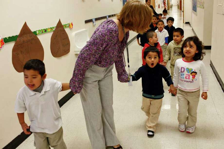 Teacher Andrea Greimel walks with her students including Harry Nunez, 3, (from left) Anthony Moreno, 3, and Jacquelin Ramirez, 3, at Carvajal Early Childhood Education Center. Photo: LISA KRANTZ, SAN ANTONIO EXPRESS-NEWS / SAN ANTONIO EXPRESS-NEWS
