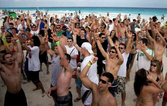 FILE-   This Monday, March 1, 2010 file photo shows students on spring break cheering at the beach in the resort city of Cancun, Mexico. Despite headlines about Mexico's violent drug war, tourism remains relatively string this year and Cancun is still expecting spring-breakers.   (AP Photo/Israel Leal, FILE) Photo: Israel Leal, STR / AP