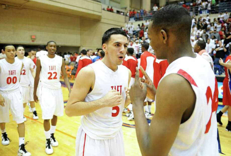 San Antonio Taft's Carlos Gutierrez (5) celebrates with San Antonio Taft's Deondre Logan (24) after the 5A boys regional semifinal basketball game between the San Antonio Taft Raiders and the Edinburg Bobcats in the UTSA Convocation Center in San Antonio, Texas on March 4, 2011  John Albright / Special to the Express-News. Photo: JOHN ALBRIGHT, San Antonio Express-News / San Antonio Express-News