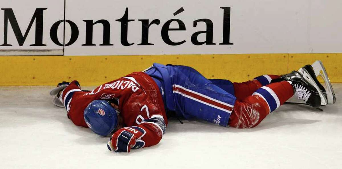 Montreal Canadiens' Max Pacioretty lays on the ice after taking a hit by Boston Bruins' Zdeno Chara during the second period of an NHL hockey game, Tuesday, March 8, 2011, in Montreal.