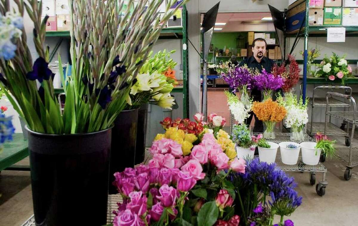 Teddy Gianokos, President of Peter's Wholesale Florist, wheels racks of flowers into the cooler at his location in Stamford, Conn. on Wednesday March 9, 2011.