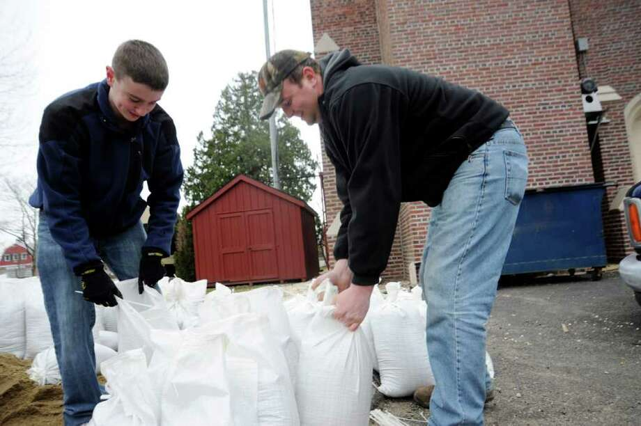 Brothers Kevin, left, and Billy Ingraham, both Cos Cob volunteer firefighters, bag sand in preparation for Thursday's rain storm at the Cos Cob Volunteer Fire Company, on Wednesday, March 9, 2011. Photo: Helen Neafsey / Greenwich Time