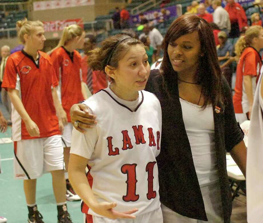 With the Lamar Lady Cardinals winning 81-77, #11, Jenna Plumley, left, walks off the court with Assistant Coach Ashley Crawford, right, as they head to the locker room.  Dave Ryan/The Enterprise / Beaumont