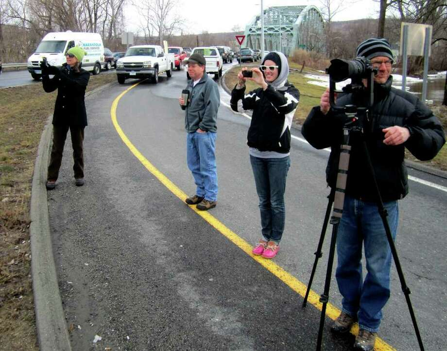 SPECTRUM/Flooding throughout the Greater New Milford area closed Route 7 from Veterans Memorial Bridge to its north intersection with Sunny Valley Road. Above, free-lance photographer Kevin Doyle, right, of New Milford surveys the flooding while Sarah Noble Intermediate School sixth-grade teacher Carol Allison, left, shoots video to show her students and her daughter, University of Connecticut junior Kate Allison shoots photos. Between the Allison women is fellow New Milford resident Frank Reidl. The numerous vehicles parked on Bridge Street near the bridge were moved there temporarily by neighboring businesses. The worst may be yet to come as police report the Housatonic River isn't expected to crest until early Tuesday afternoon. March 7, 2011 Photo: Norm Cummings / The News-Times