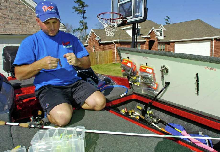 Kyle Swearingen, a Lumberton resident who won a recent bass fishing tournament was on his boat Wednesday, though parked in his driveway, checking and stowing some of his fishing equipment.  Dave Ryan/The Enterprise / Beaumont
