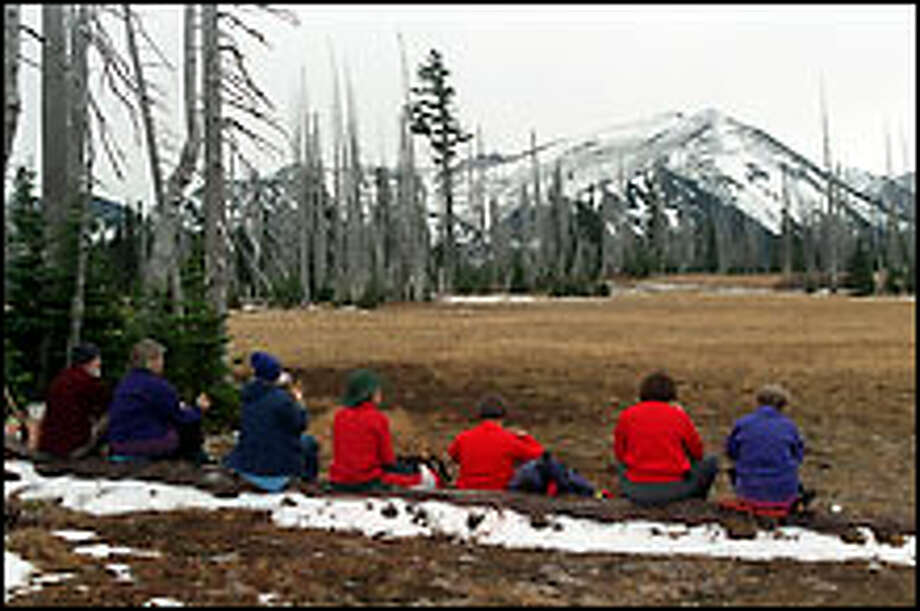 """Seating with a view: Hikers pause for lunch in Grand Park while soaking up the vista of snow-dusted Mount Fremont in Mount Rainier National Park. The """"unofficial"""" approach via Lake Eleanor from national forest land north of the park is shorter and easier than the official route from Sunrise. Photo: Karen Sykes/Special To The Post-Intelligencer"""