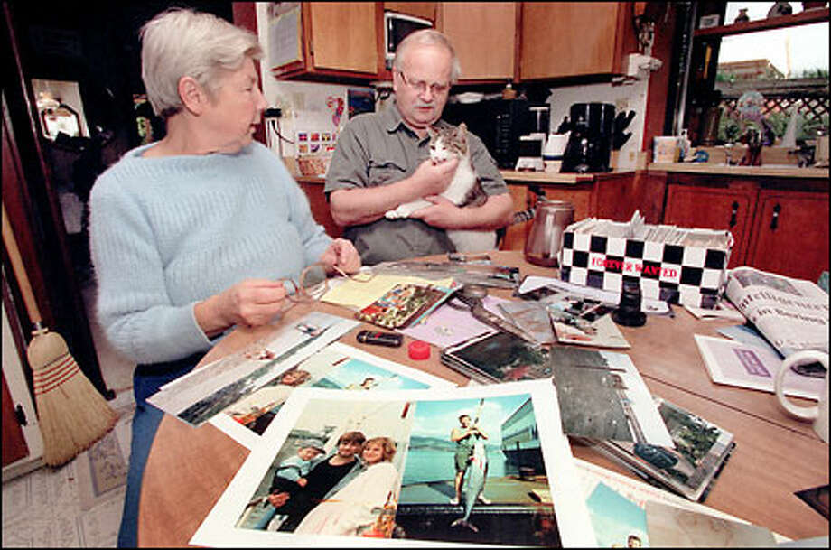 "Lou Anne and David Rundall sort through family photos in preparation for a memorial for their son, ""Davy,"" the skipper of the Arctic Rose. Photo: Grant M. Haller/Seattle Post-Intelligencer"
