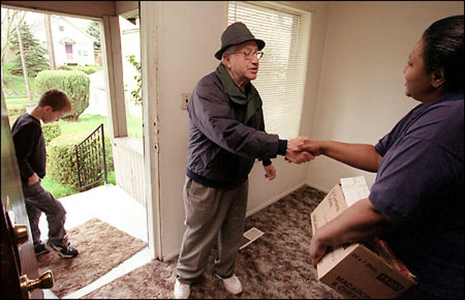 Jefferson Award Winner Lou DeFranco delivers a food donation to Mary Wilson in Columbia City as helper Paul Loranger waits in the doorway. DeFranco has been a civic activist and community leader in Rainier Valley for more than 50 years. Photo: Meryl Schenker/Seattle Post-Intelligencer