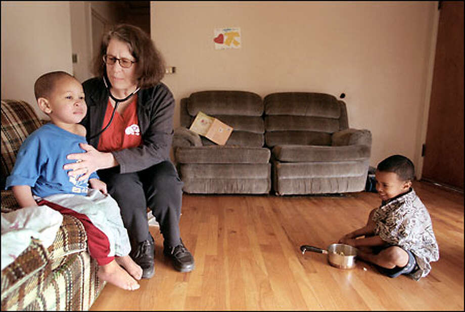 Markie Branch, 2, gets a checkup from Lois Thetford while his brother Jasiri, 4, watches. Through the Pathways Home program, which Thetford helped start, homeless families in transition can get home health care. Photo: Meryl Schenker/Seattle Post-Intelligencer