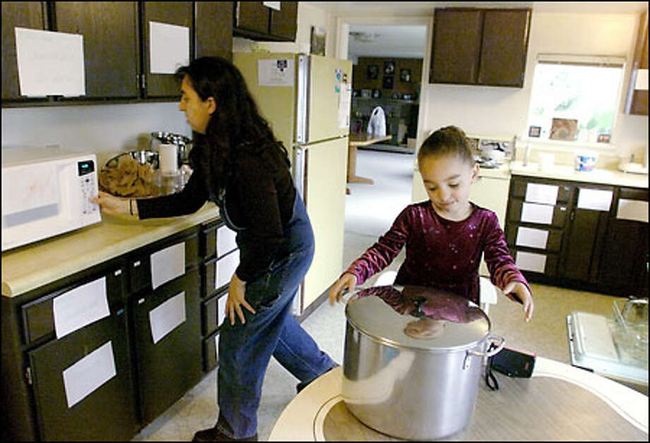 Danielle Yancey prepares for Passover with the help of her daughter Michaela, 3, in their Lake Forest Park home. The signs on the cupboards mark the ones that have been cleaned. Photo: Meryl Schenker/Seattle Post-Intelligencer