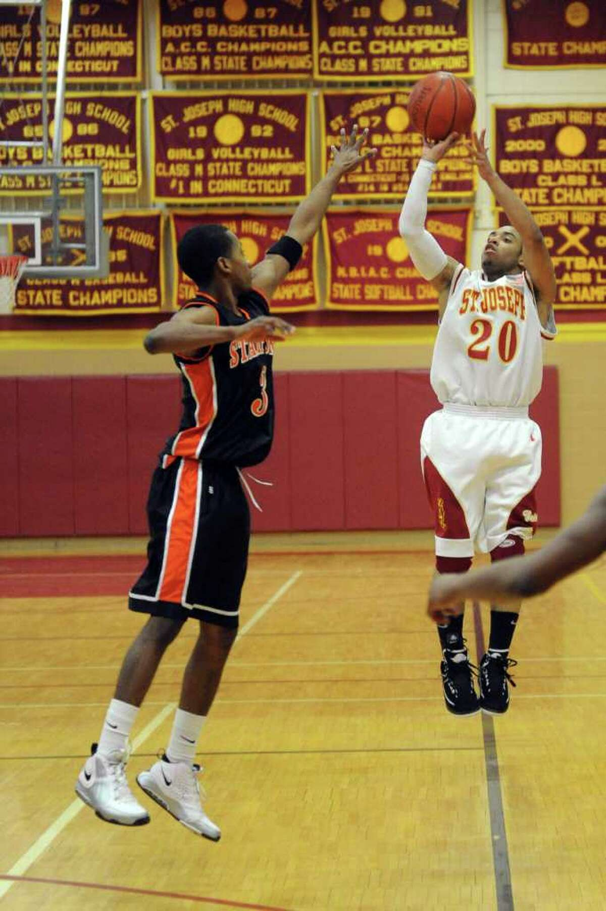St. Joseph's James Jennings takes a shot as Stamford's Anthony Davis reaches to block during Wednesday's game at St. Joseph's High School on March 9, 2011.