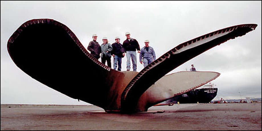 On top of a 92,750-pound, 27-foot-diameter spare wheel (propeller) from the Overseas New Yorker they are storing in Port Angeles, are from left, Prime's Jim Mattix, Lynn Mattix, Rich Harris, Corby Somerville and Dan Sessler. Photo: Grant M. Haller/Seattle Post-Intelligencer