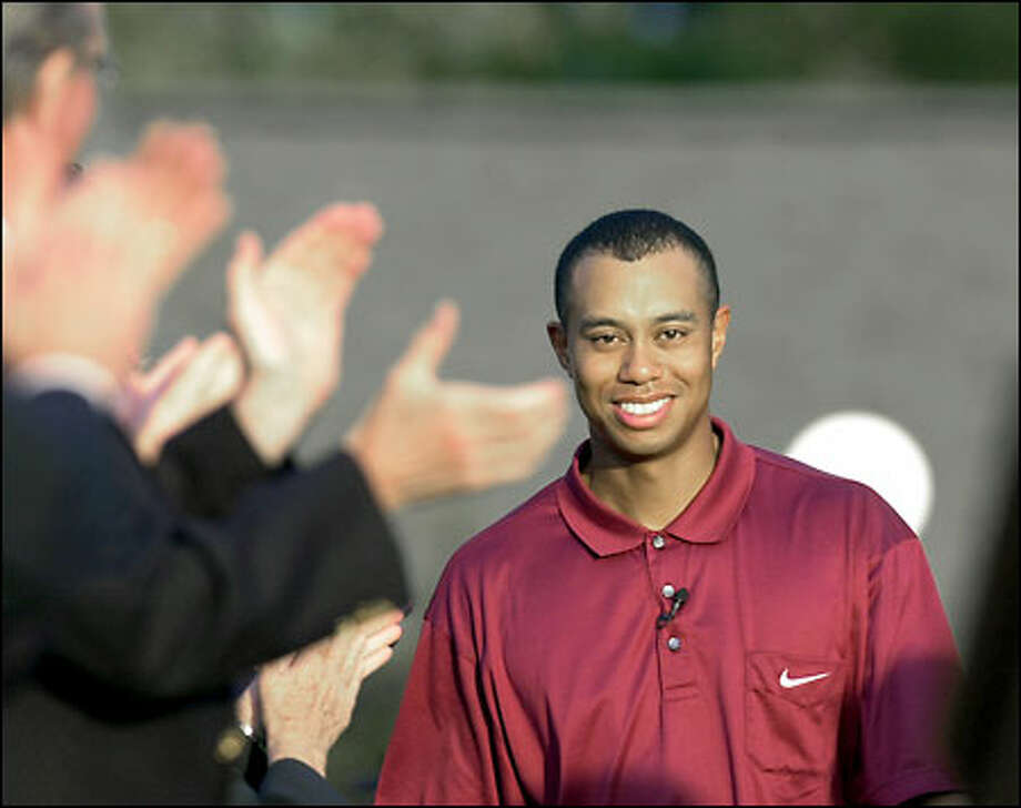 Tiger Woods is applauded as he arrives at the green jacket ceremony after winning the Masters at Augusta National Golf Club. Woods has won golf's past four major championships and five of the past six. Photo: / Associated Press