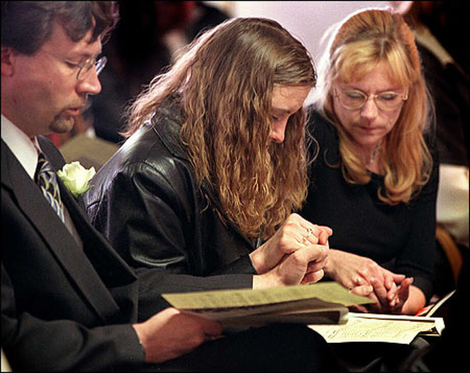 Dwayne Barch, Trinity Wandler and Julie Barch hold hands during memorial services for Jimmie Conrad. Barch was Conrad's stepfather; Wandler was Conrad's girlfriend. Photo: Grant M. Haller/Seattle Post-Intelligencer