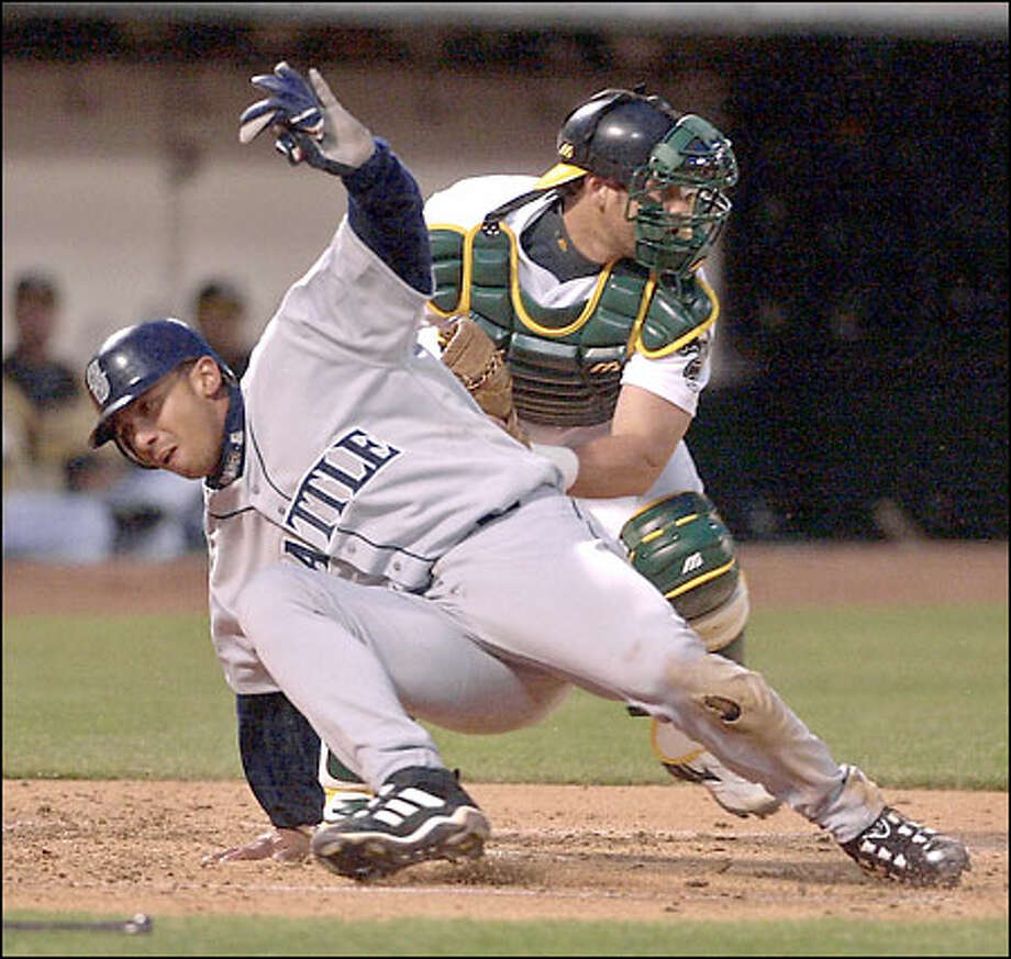 Carlos Guillen beats the tag of Oakland catcher Ramon Hernandez to score the Mariners' first run in the second inning. Photo: / Associated Press