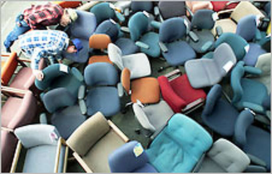 Sam Warren and Mike McDougall, both of Everett, search a sea of chairs for a bargain during the Ducky's Office Furniture sale. Photo: Mike Urban/P-I