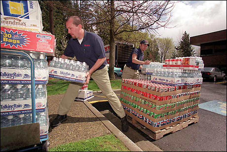 Paul Johnson, left, and Troy Harthun, delivery drivers for Costco Business Center, unload and organize soda pop and bottled water yesterday at Edifecs Commerce in Bellevue. Photo: Phil H. Webber/Seattle Post-Intelligencer