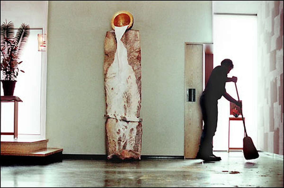 Tom Lewis sweeps up after he and three others installed the 2,300-pound marble sculpture at center in Seattle University's Chapel of St. Ignatius.