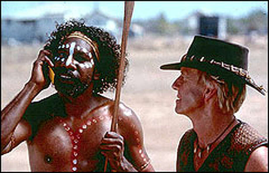 Mick Dundee (Paul Hogan, right) may not be completely connected to the 21st-century world but his friend Arthur (David Ngoombujarra, left) obviously is.