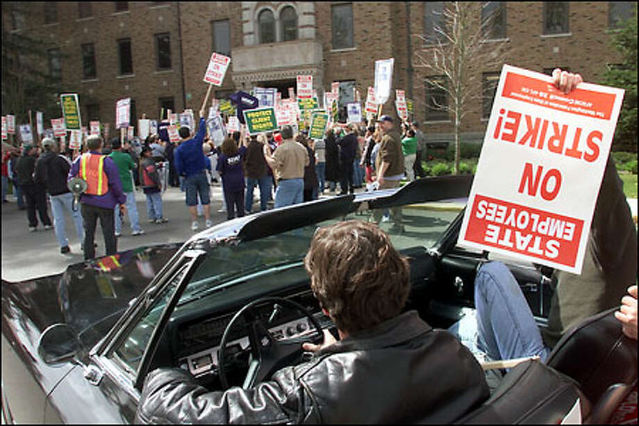 Western State Hospital employee Scott Ault holds a strike sign in Doug Davidson's car as they join fellow state workers at a Steilacoom rally yesterday. Photo: Paul Kitagaki Jr./Seattle Post-Intelligencer