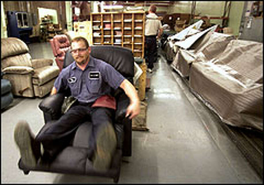 Tim Nelson kicks back in a La-Z-Boy recliner at the company's plant in Dayton, Tenn. Although sitting in chairs all day may seem like the perfect way to combine work and relaxation, inspectors say it is really rather strenuous. Photo: AP