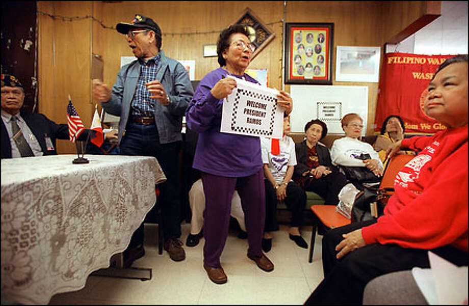 Dolly Castillo, center, social director for the International Drop-in Center in Seattle, leads the members in a song before a visit by former Philippine President Fidel Ramos. Photo: Grant M. Haller/Seattle Post-Intelligencer