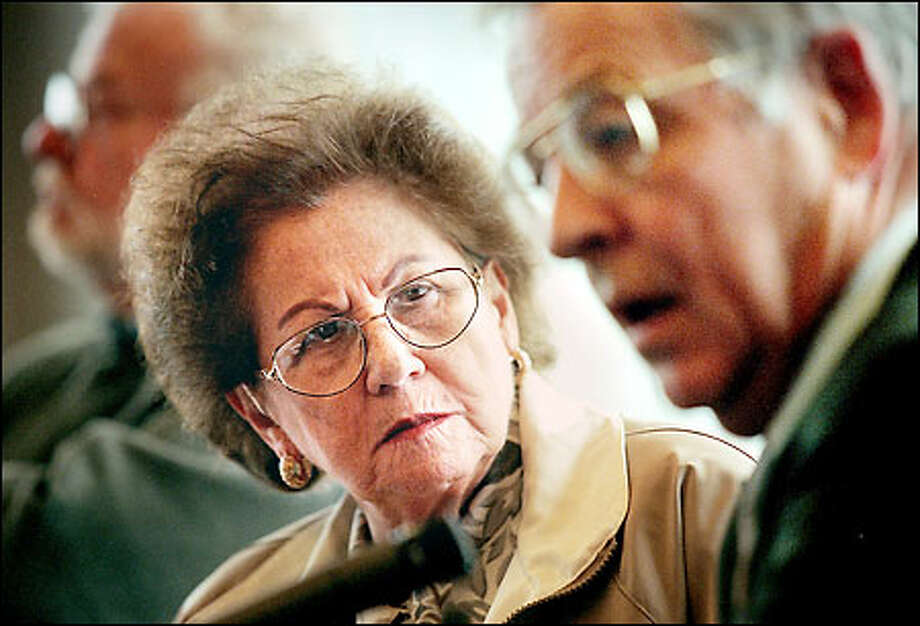 """Magda Schaloum, a Hungarian Jew who, as a young woman, was herded onto a train bound for Auschwitz, listens to Leo Hymas talk of liberating a concentration camp in World War II. The two spoke at the """"Afternoon of Memoirs"""" program at REI yesterday. Photo: Dan DeLong/Seattle Post-Intelligencer"""